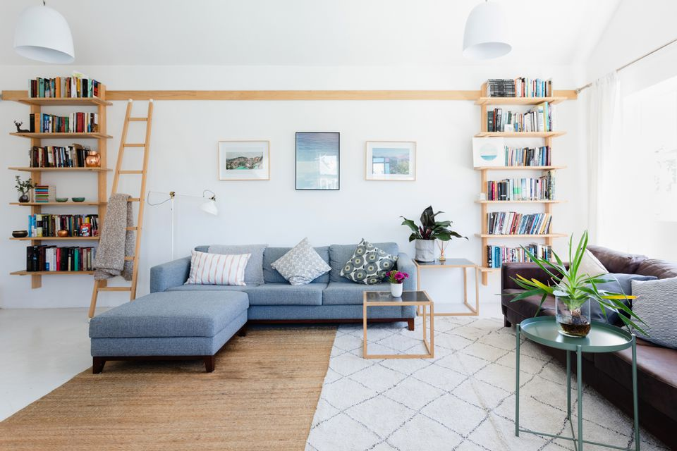Brightly lit living room decorated with bookshelves and pillows