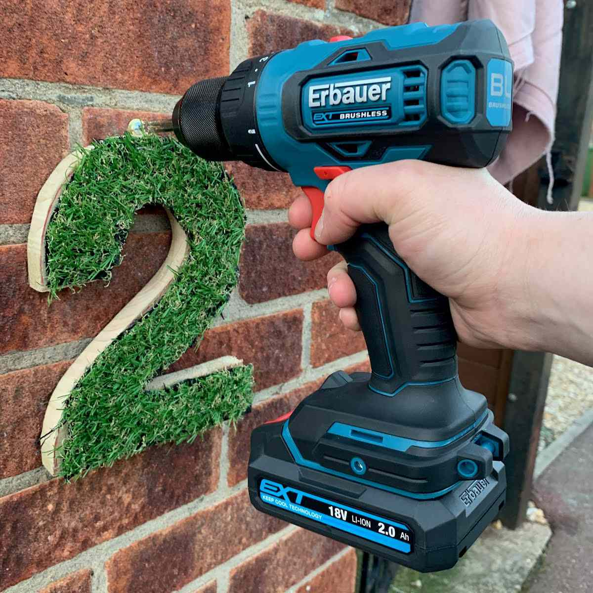 Grass house numbers drilled onto brick.