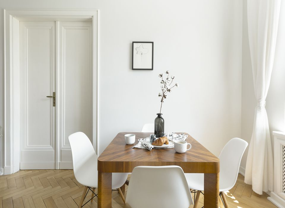 White chairs at wooden table in minimal dining room interior with door and poster.