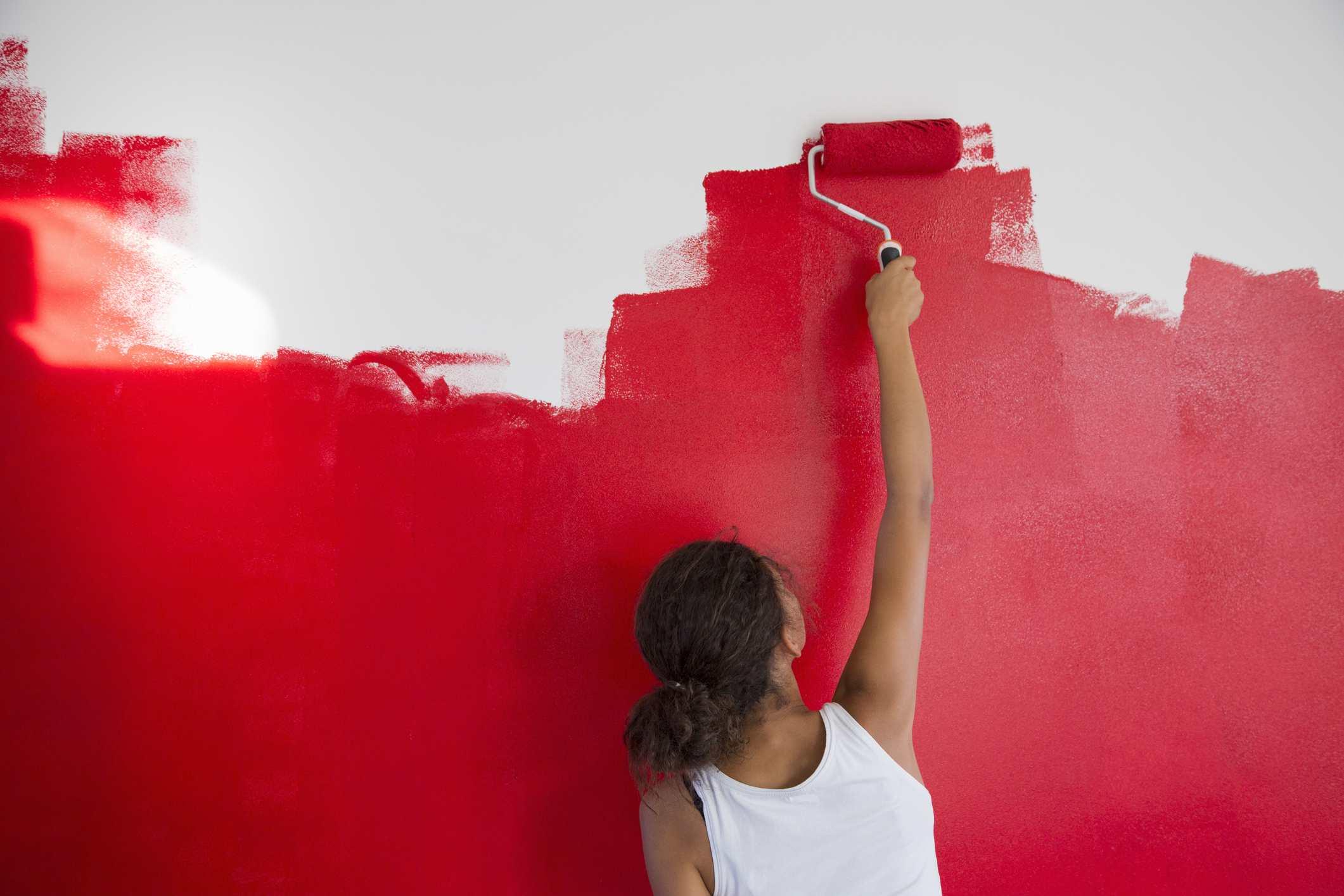 Vista posterior de una niña que pinta la pared roja con un rodillo de pintura