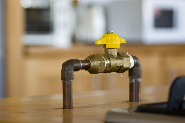 Gas shut-off ball valve in a kitchen with blurry background