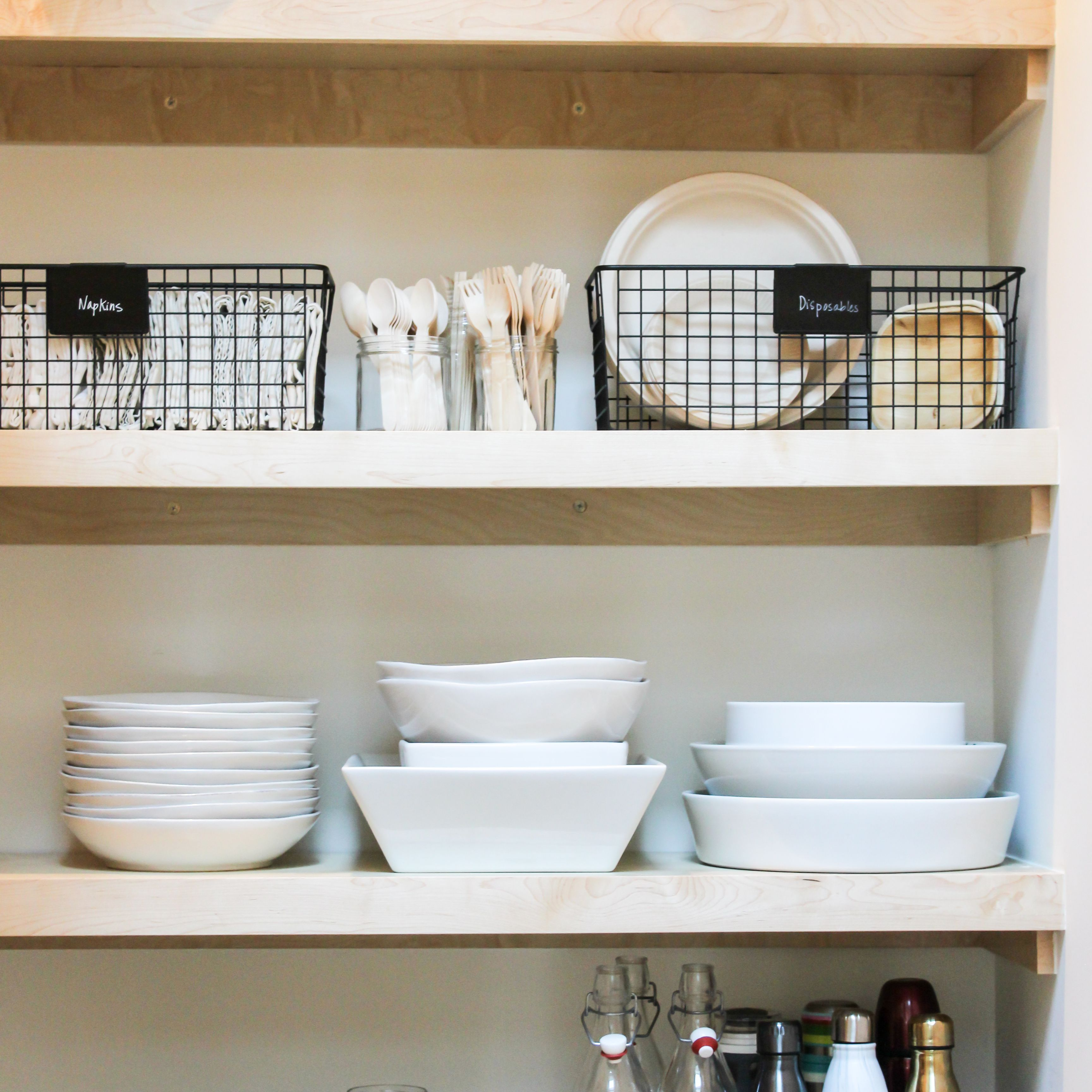Shelving with organized plates, silverware, glasses, and water bottles