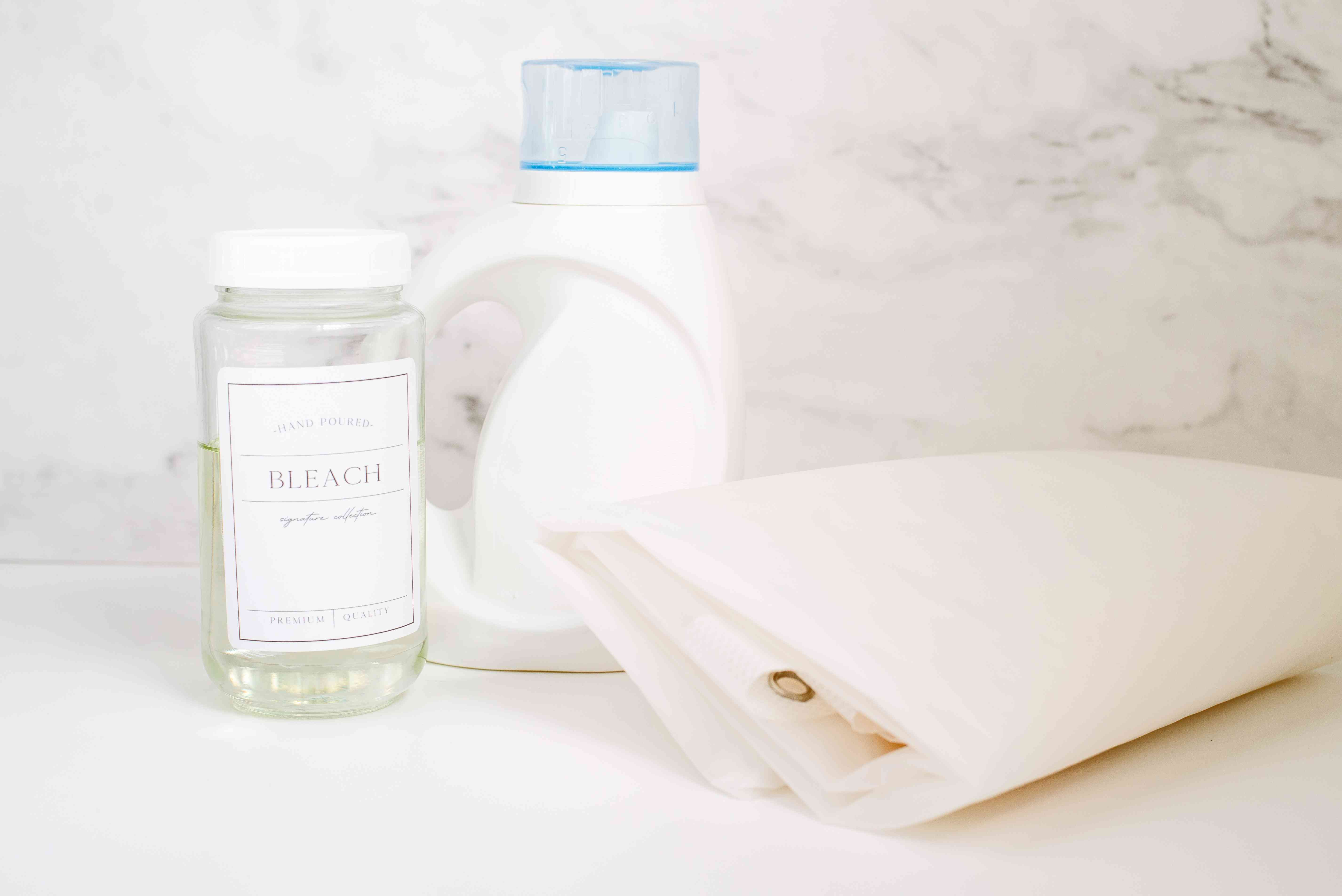Chlorine bleach in glass container next to heavy duty laundry detergent bottle and folded vinyl shower curtain