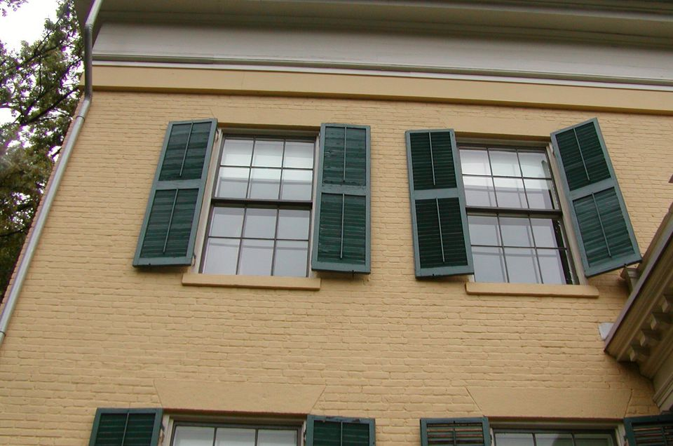 detail of second story yellow brick house with green shutters on 6-over-6 windows