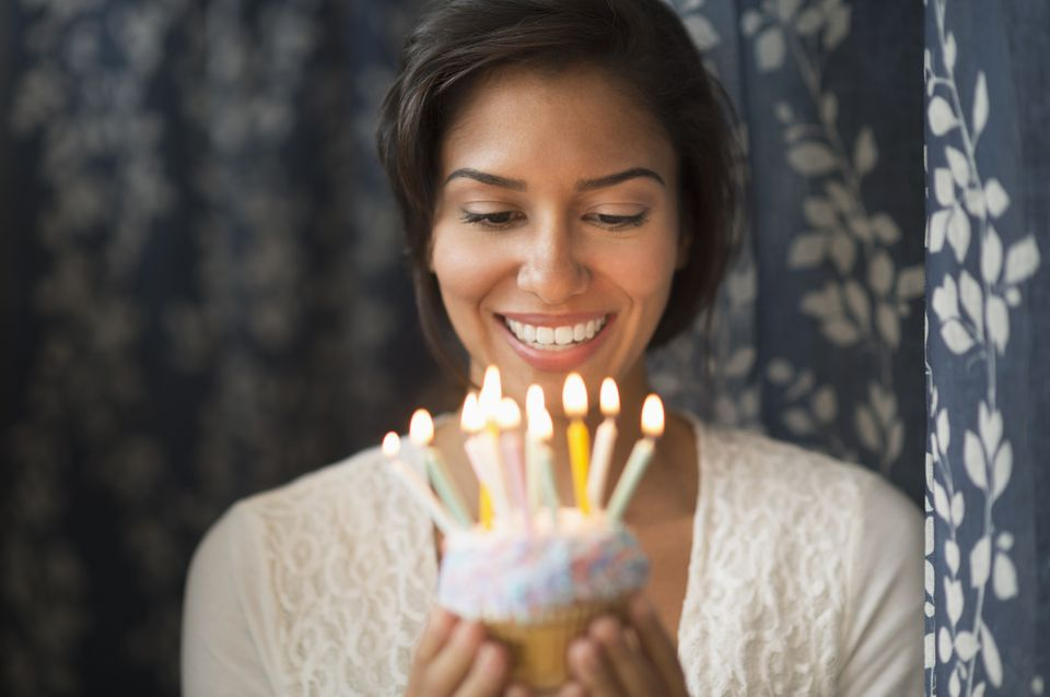 Hispanic woman looking down at lit candles on birthday cupcake