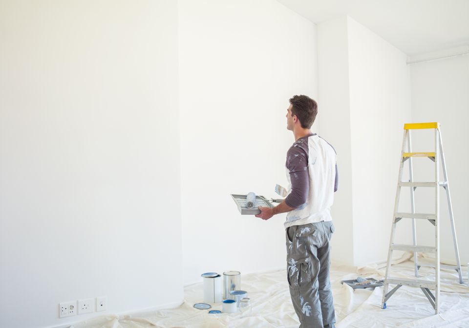 Man with paint tray looking up at white wall