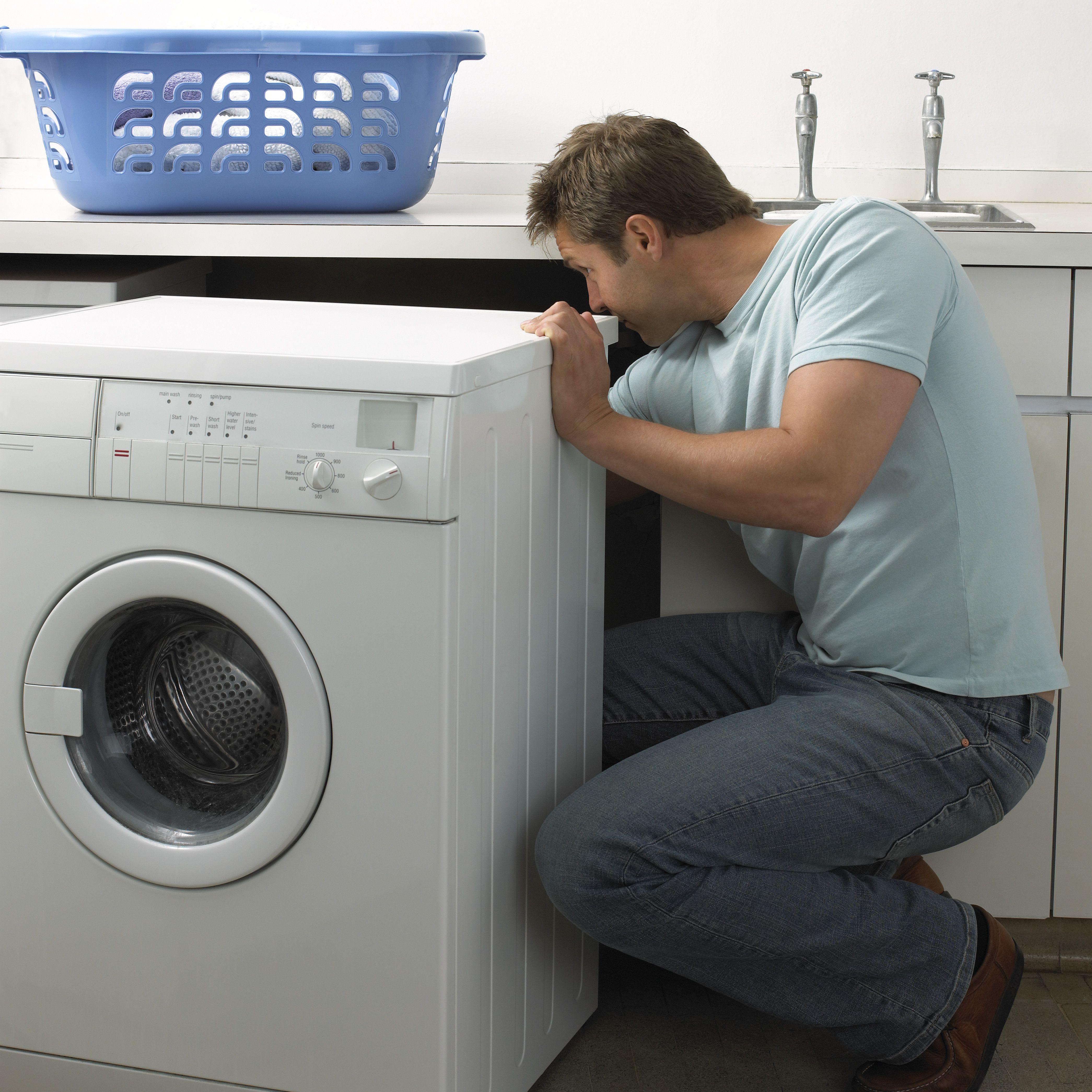 Man in a Kitchen Repairing a Washing Machine