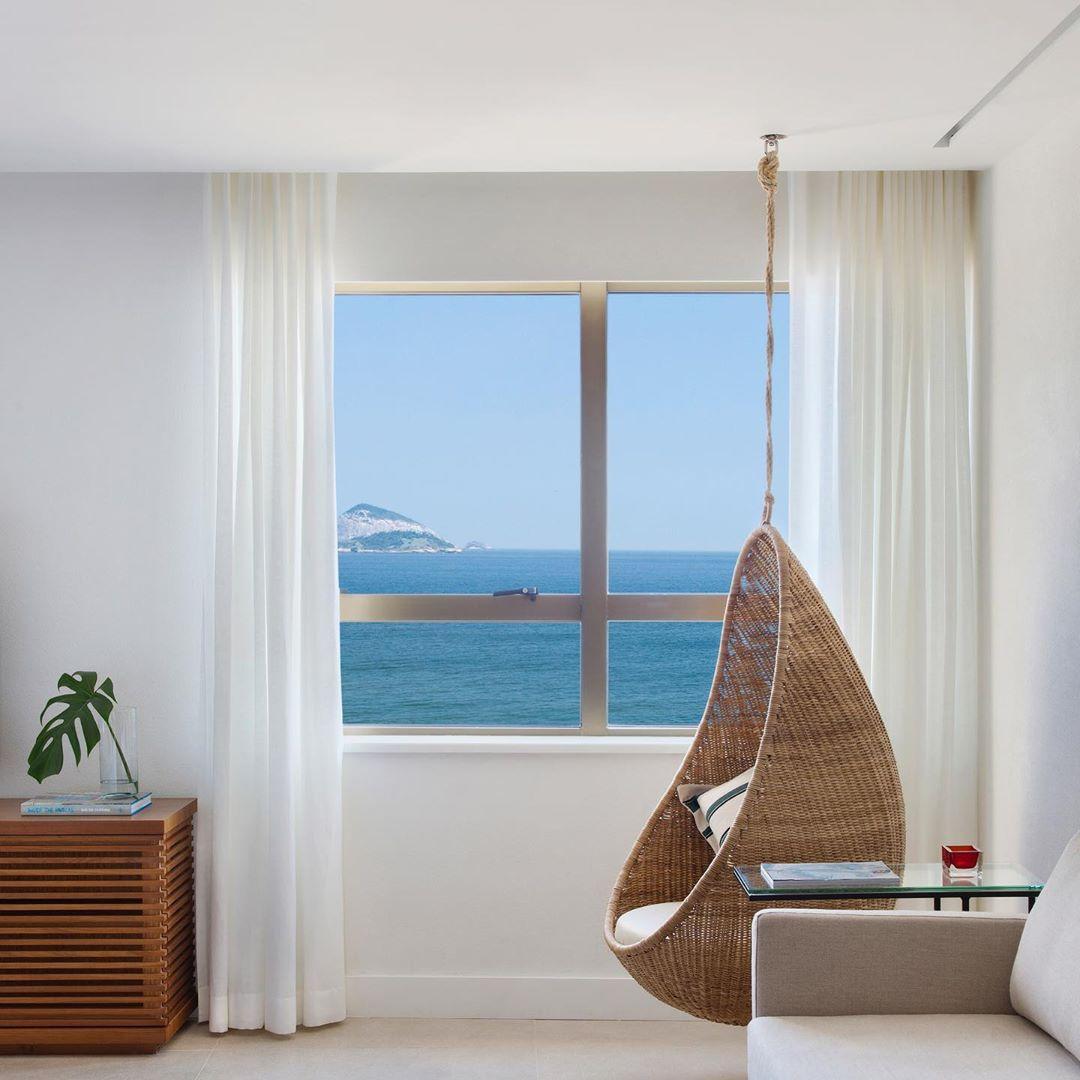 Habitación de hotel con una silla de mimbre colgante