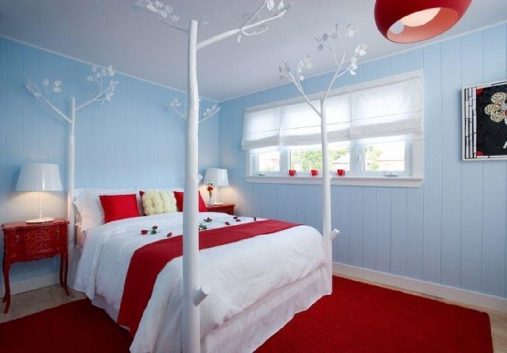 Habitación con paredes azules, alfombra roja y colcha roja y blanca