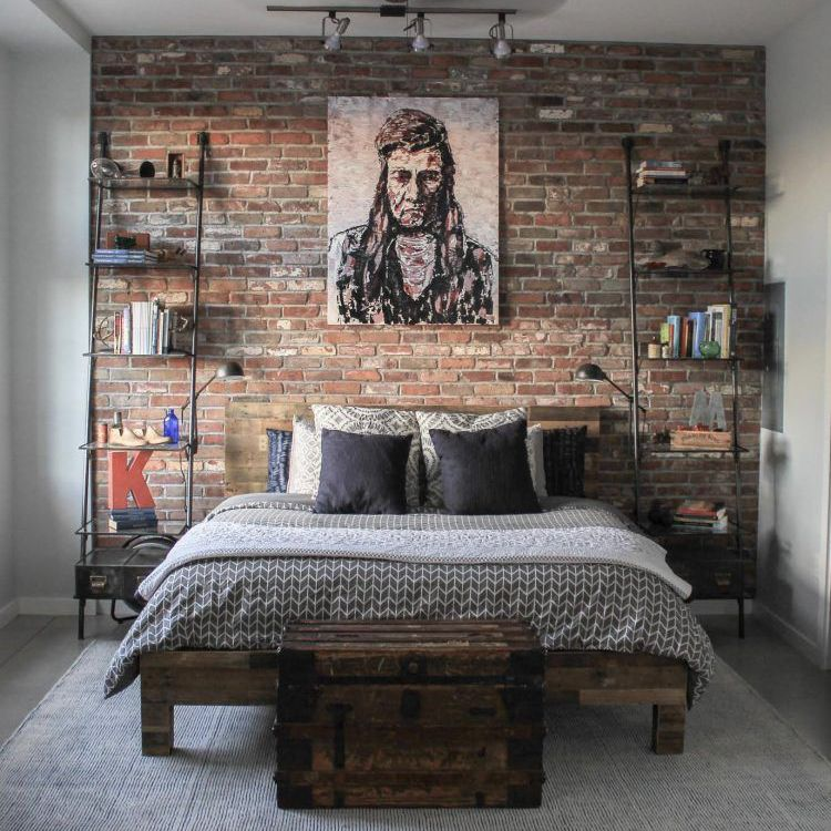 bedroom with brick wall and bookcases