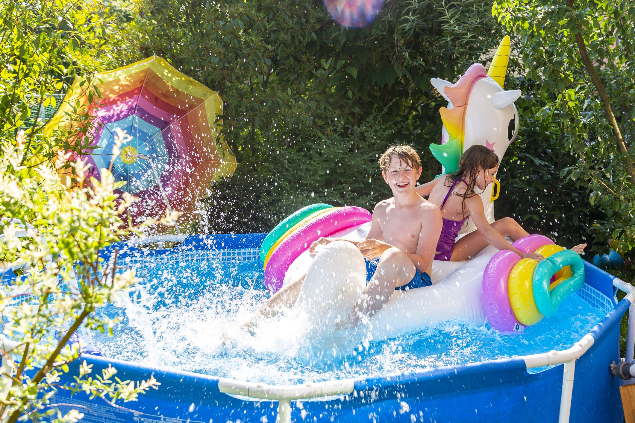 Brother and sister with oversized unicorn swim toy in paddling pool