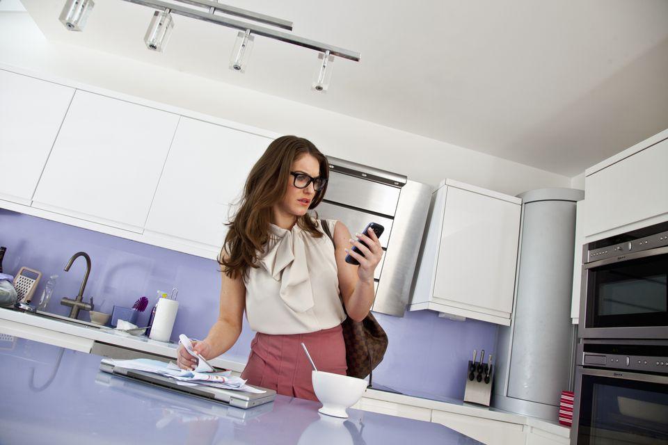 Mujer joven con teléfono celular y papeleo en el desayuno