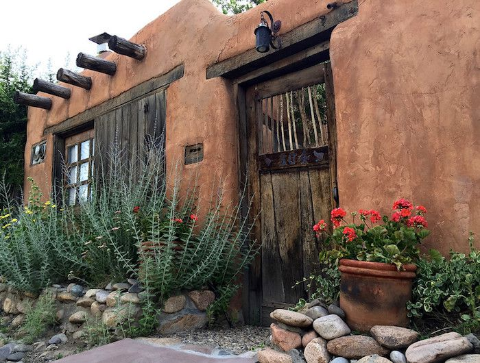 Adobe house with wooden door, Russian sage growing from rock wall by entrance and pot of red geraniums.