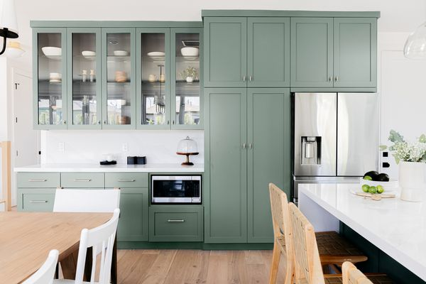 Kitchen with sage green-like painted cabinets with white marble tops and stainless steel appliances