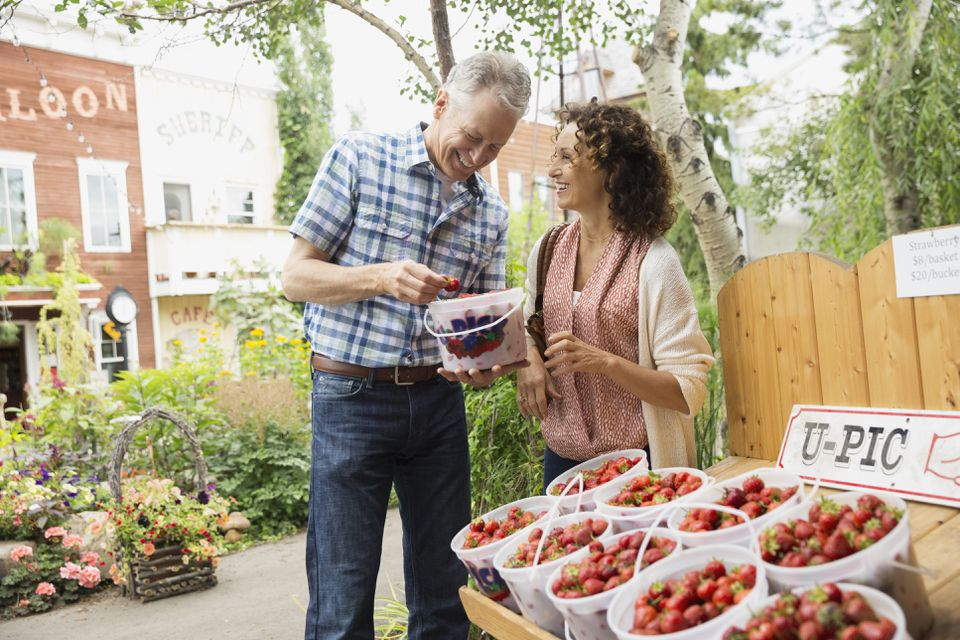 Couple shopping for berries outside farmers market