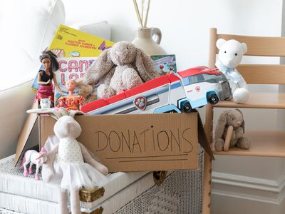 Toys stacked around donations cardboard sign