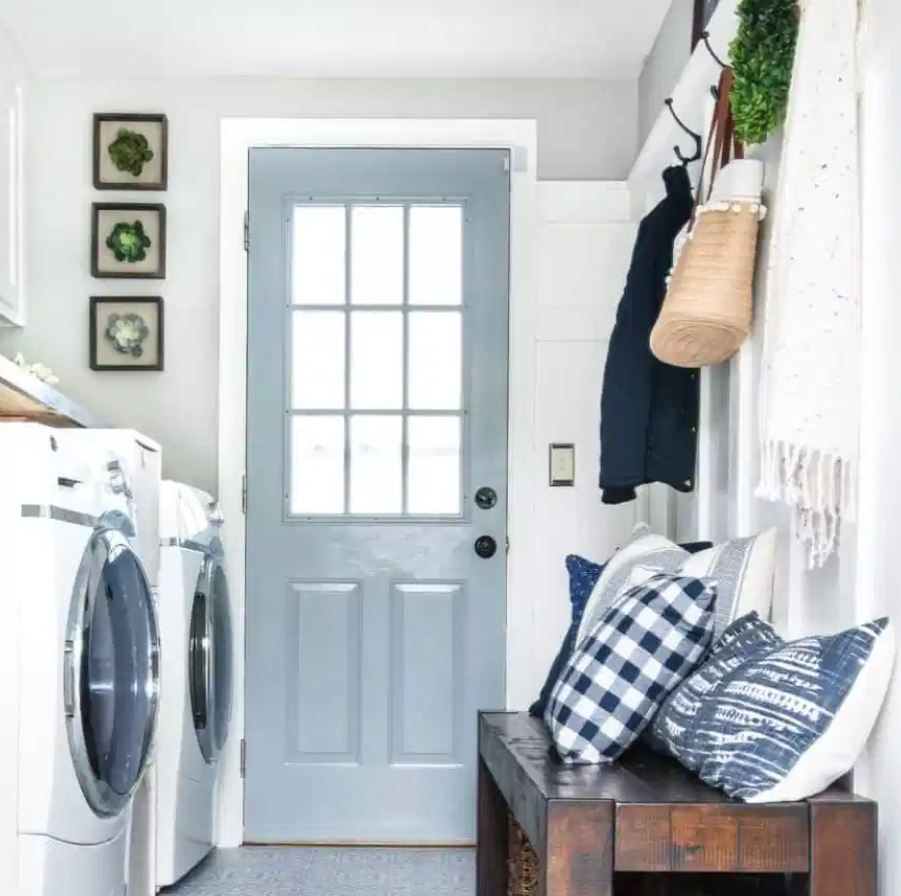 Laundry room with farmhouse style and blue door leading to outside.