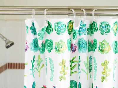 Shower curtain with water color illustrations of plants hanging in front of shower head