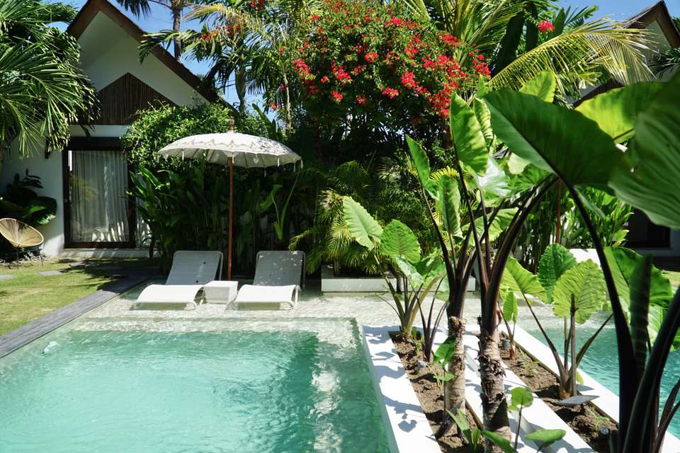 Tropical landscaping and white outdoor furniture surrounding pool