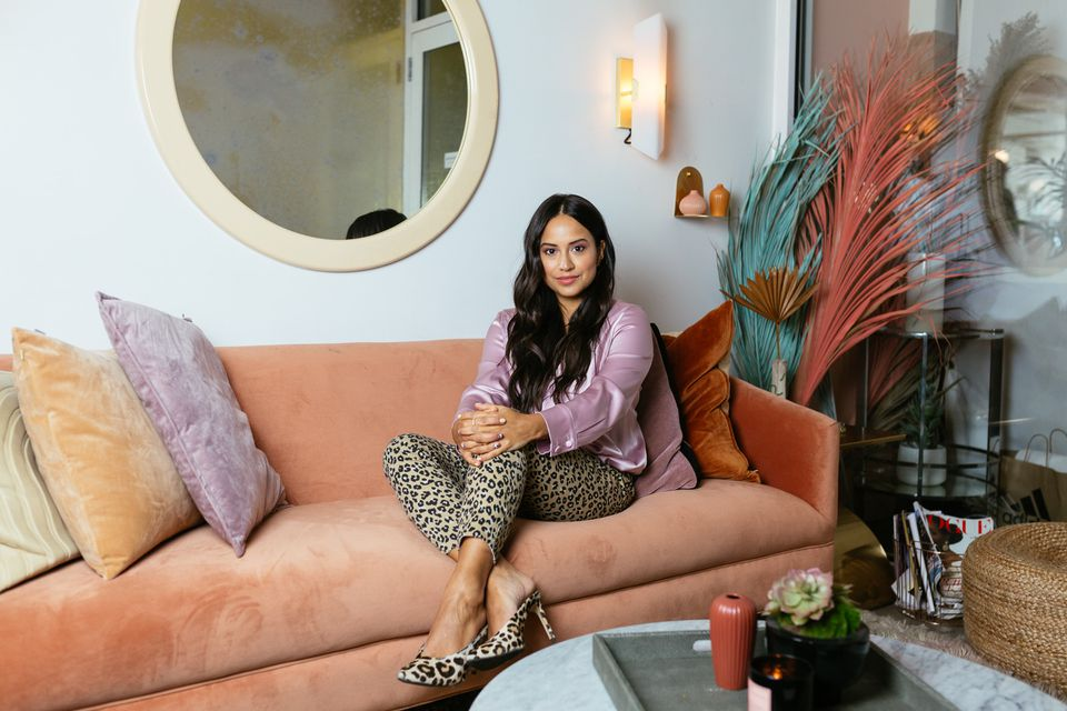 Cyndi Ramirez, founder of Chillhouse, sitting on a peach-colored couch