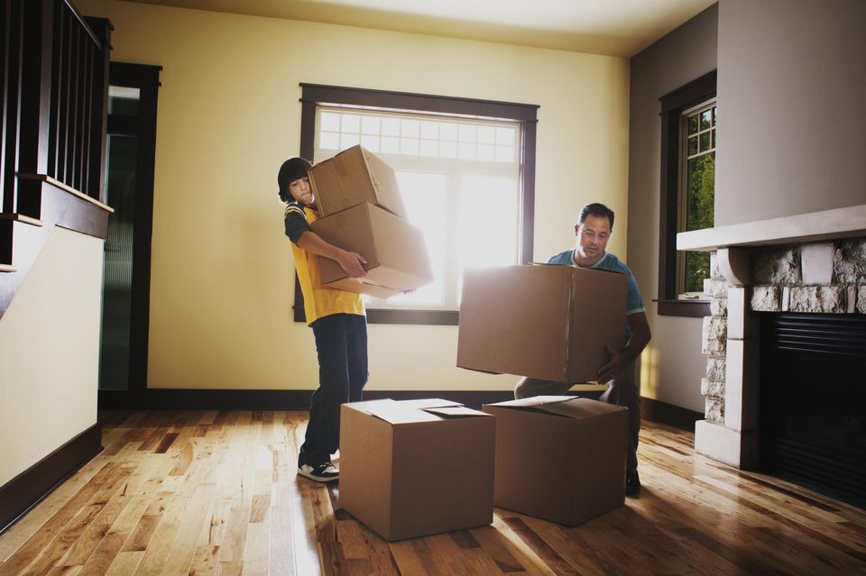 Father and son stacking boxes in a house