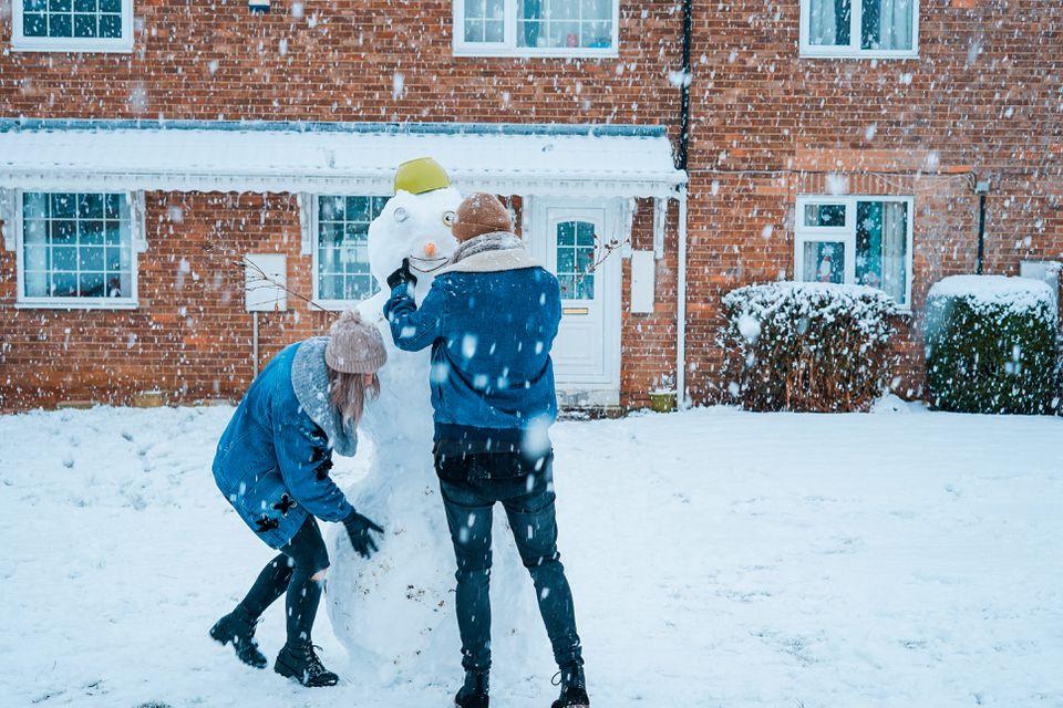 A couple building a snowman