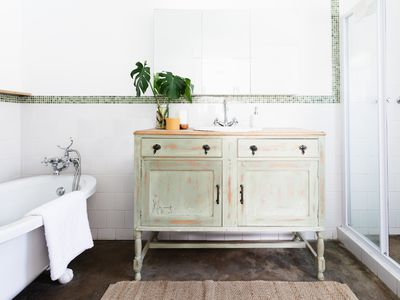 Clean bathroom with white towel hanging over tub and plant on sink surface