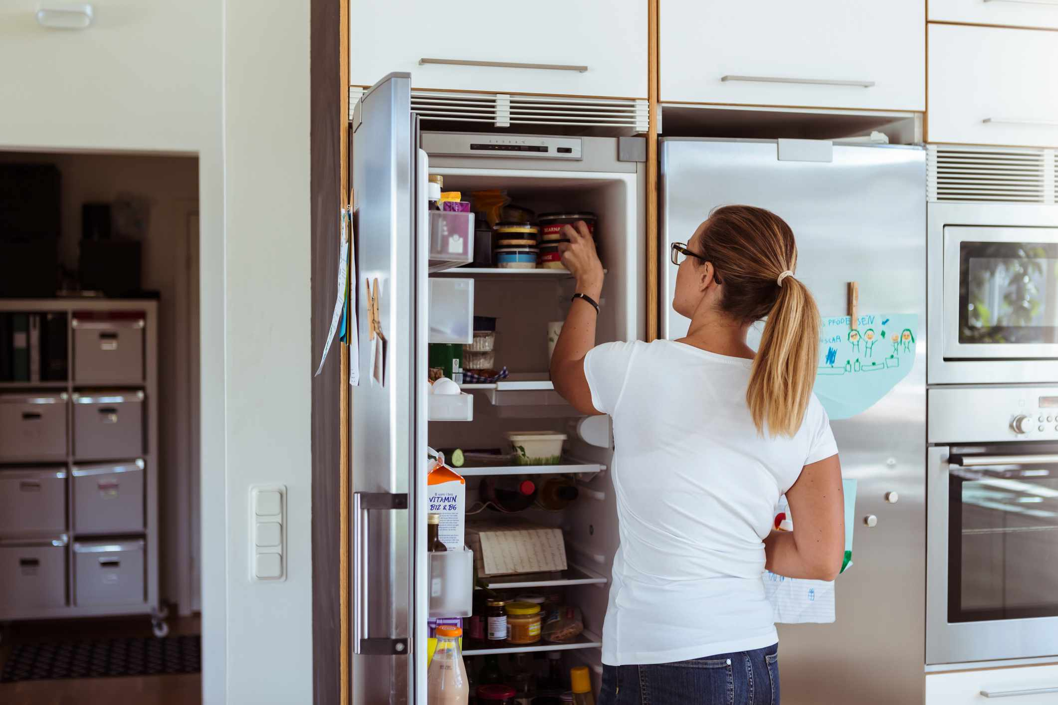 A woman organizing her refrigerator.