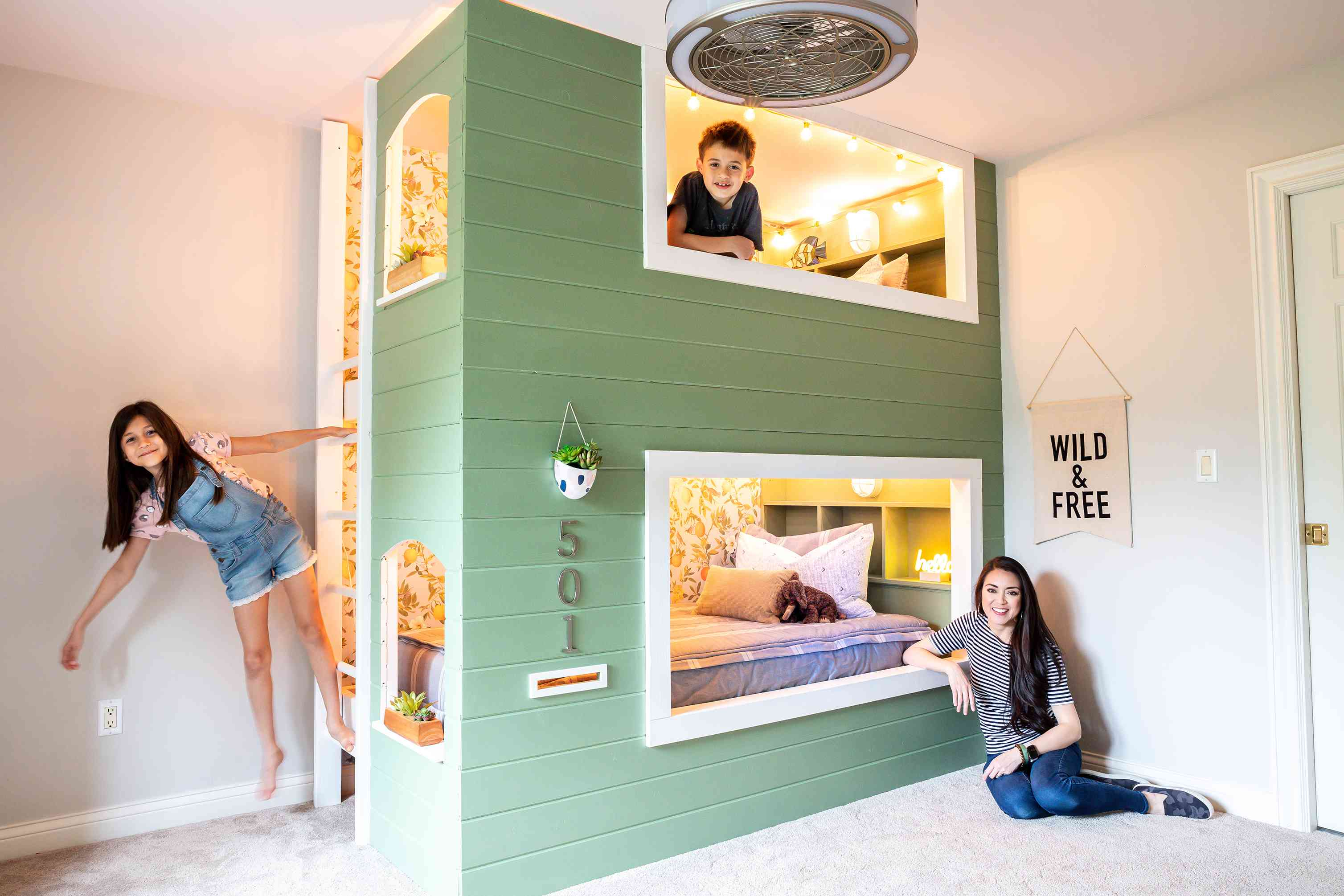 Jen Woodhouse poses with her two children next to the built-in bunkbeds she created