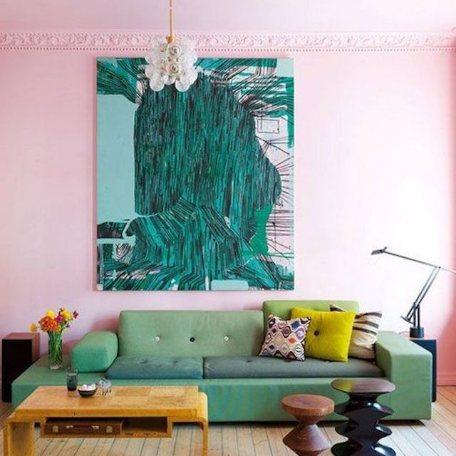 Pink room with large green artwork hanging above green sofa.
