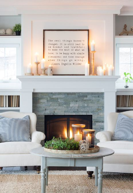 white fireplace with fire and candles on the mantle