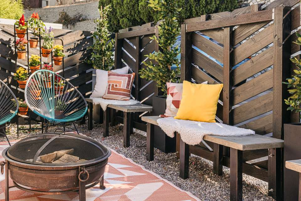 DIY privacy screen made of wood next to benches with pillows and fire pit