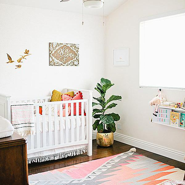 Simple, white nursery with minimal decor and a ceiling fan.