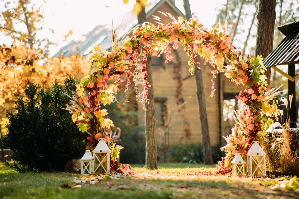Wedding arch is on the background of autumn trees and house.