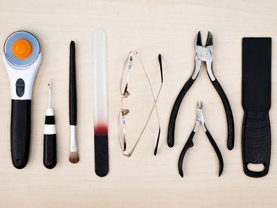 Tools and eyeglasses laid flat on wood surface and covered in black Plasti Dip