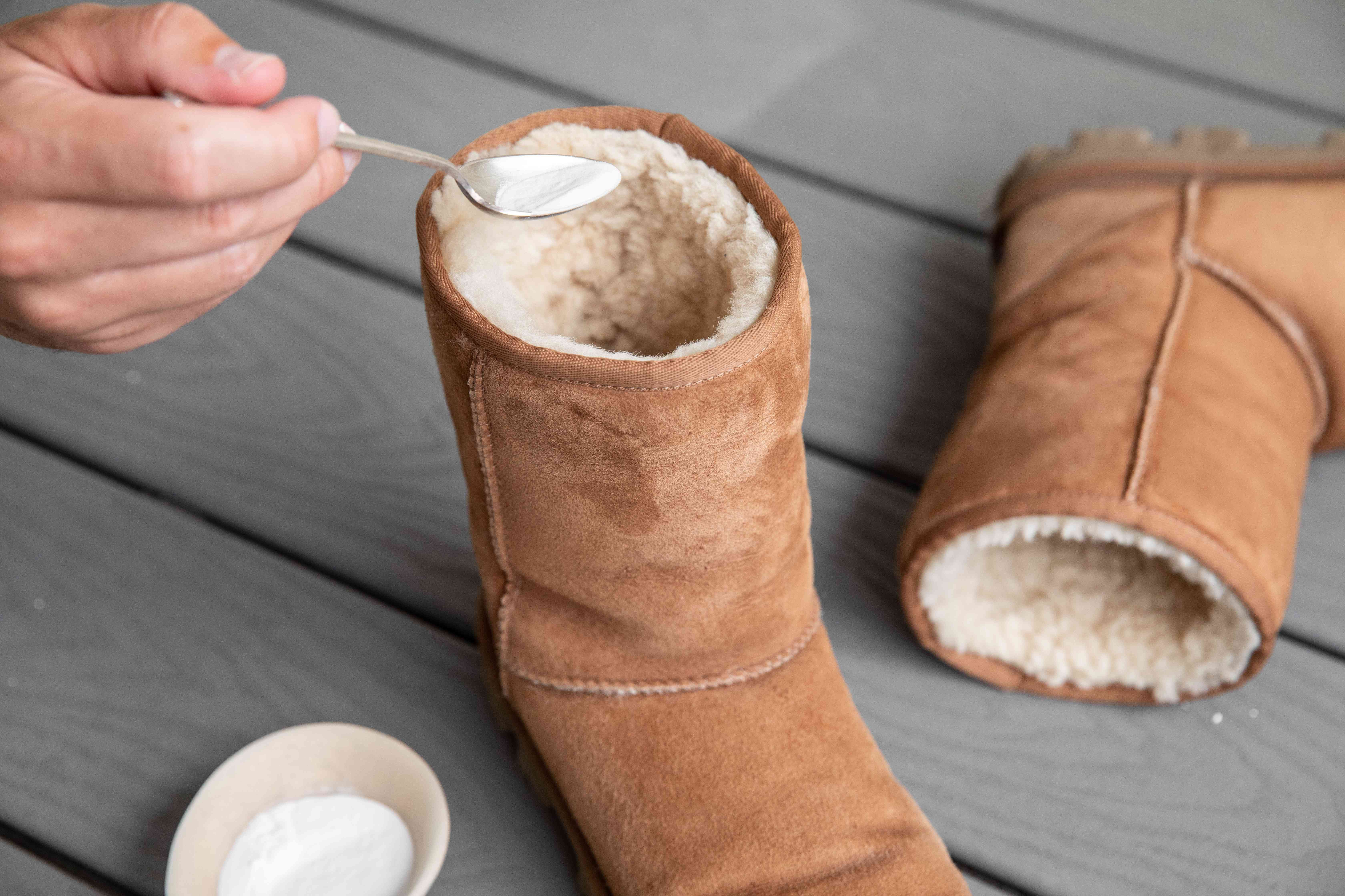 Someone spooning baking soda into an Ugg boot