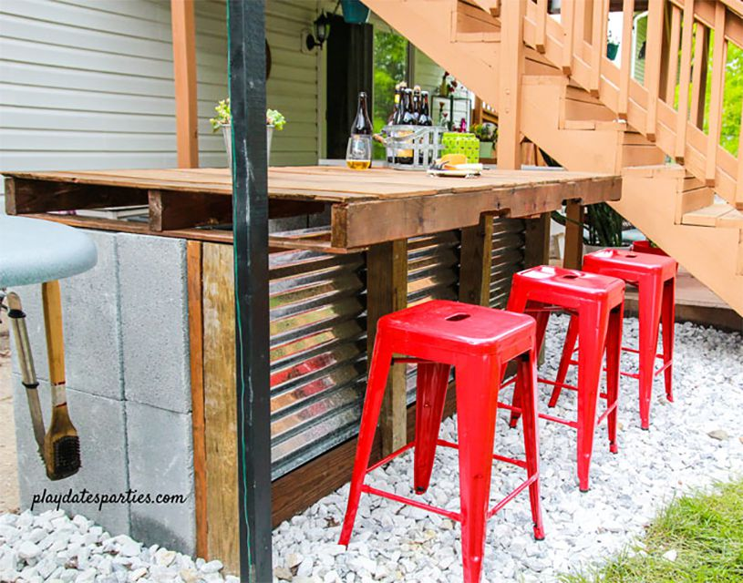 An outdoor bar made of cinder blocks with red chairs