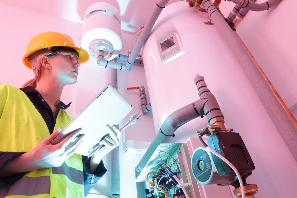 Female electrician checking boiler