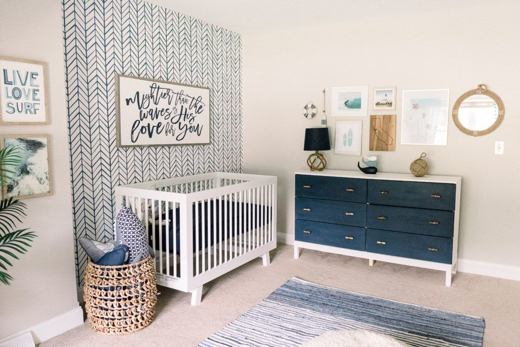 Coastal blue nursery with wallpaper accent wall.