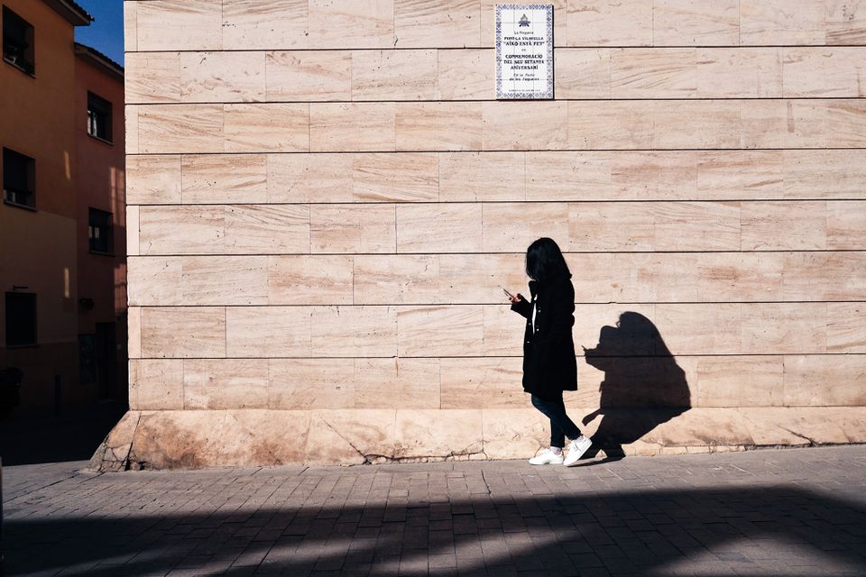 A woman walks past an exterior wall.