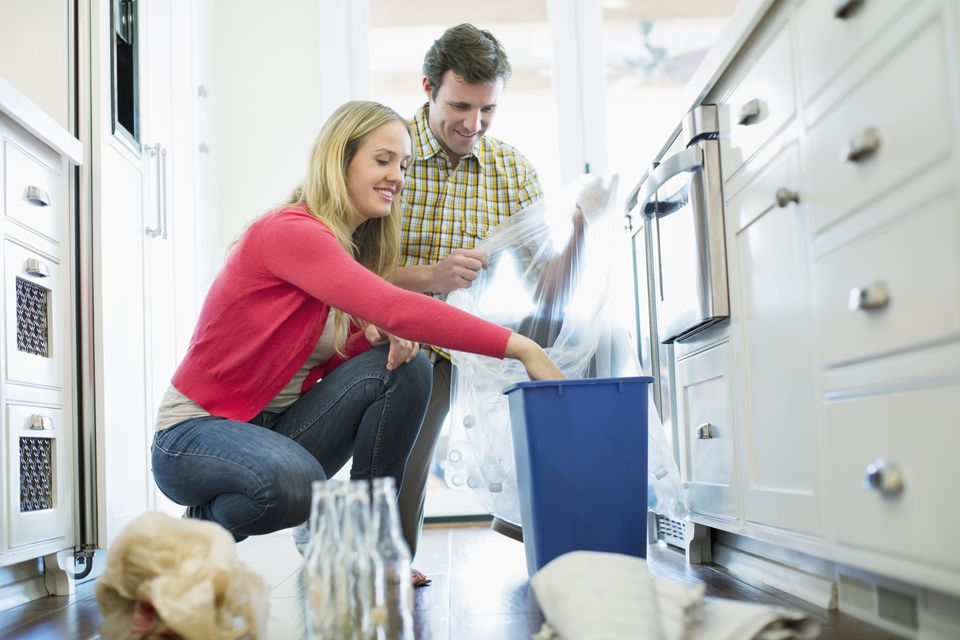 Mid adult couple recycling together in kitchen