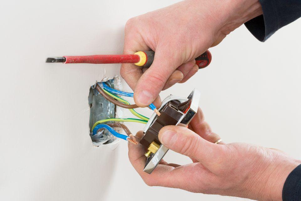 Un electricista arreglando un enchufe
