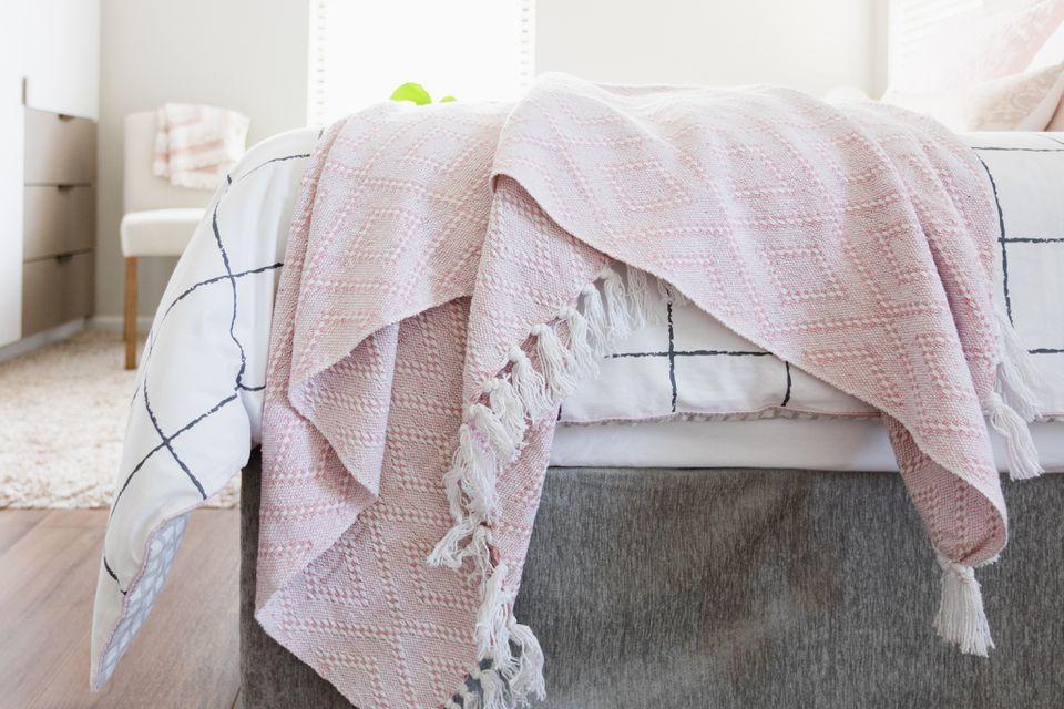 Pink throw blanket hanging off bed corner
