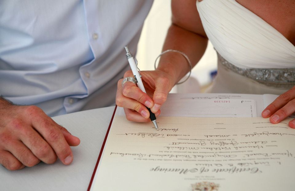 Couple signing their marriage certificate