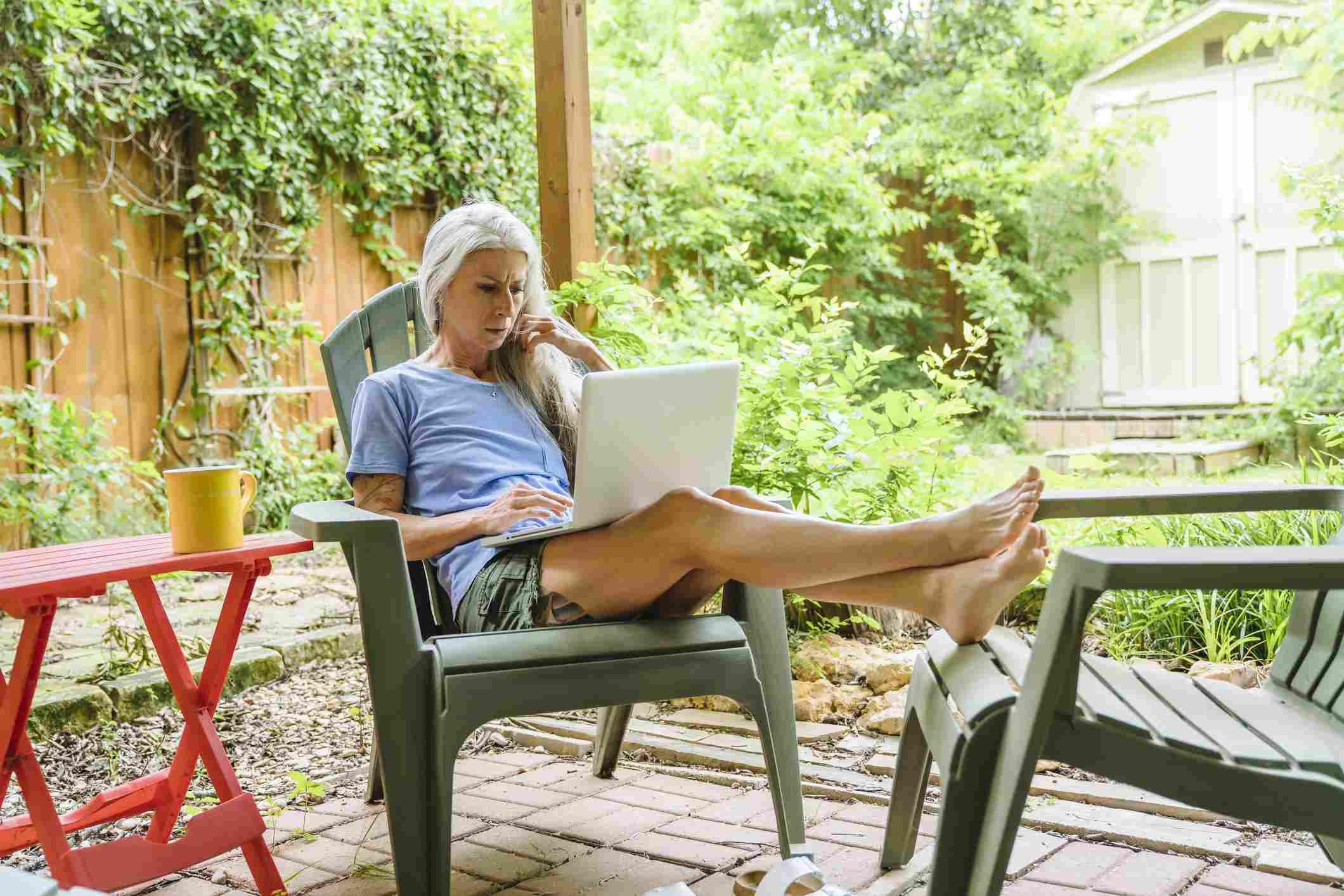Mujer trabajando en el patio trasero de la computadora portátil