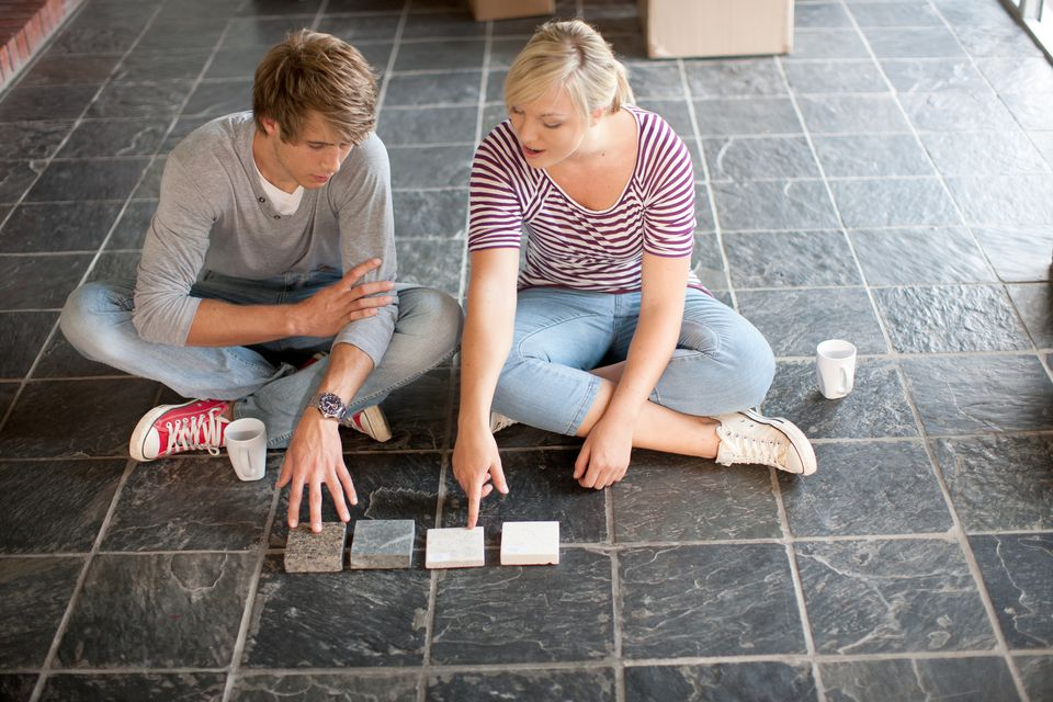 Young couple sitting on floor choosing new tiles