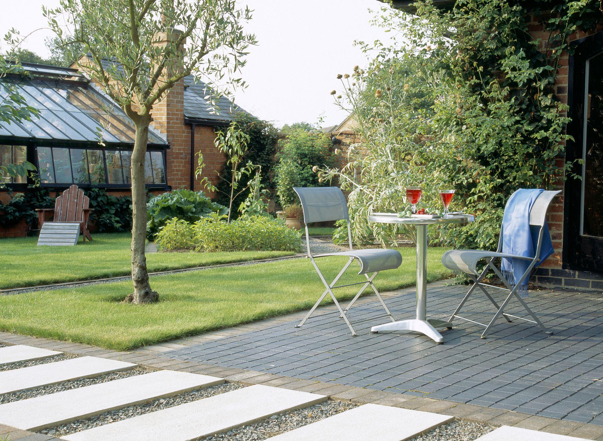 Patio de estilo moderno con mesa y sillas de metal, junto a la elegante pasarela