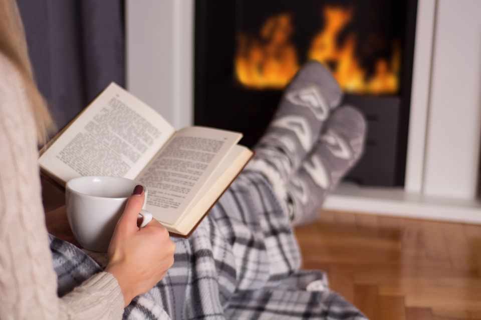 Girl in front of the fireplace reading book and warming feet on fire