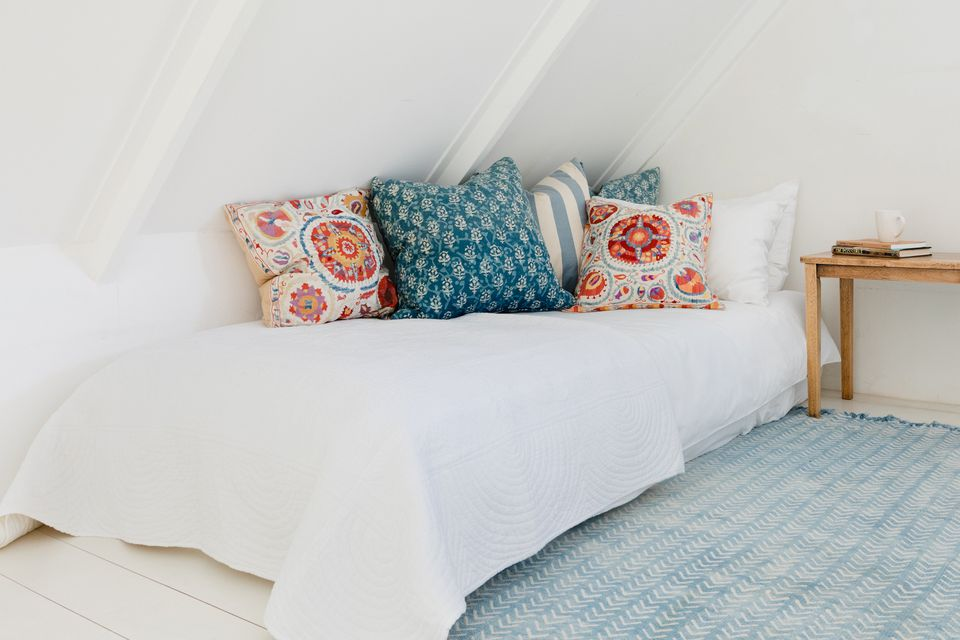 Portable floor bed covered with a white bed cover and blue and orange pillows on top