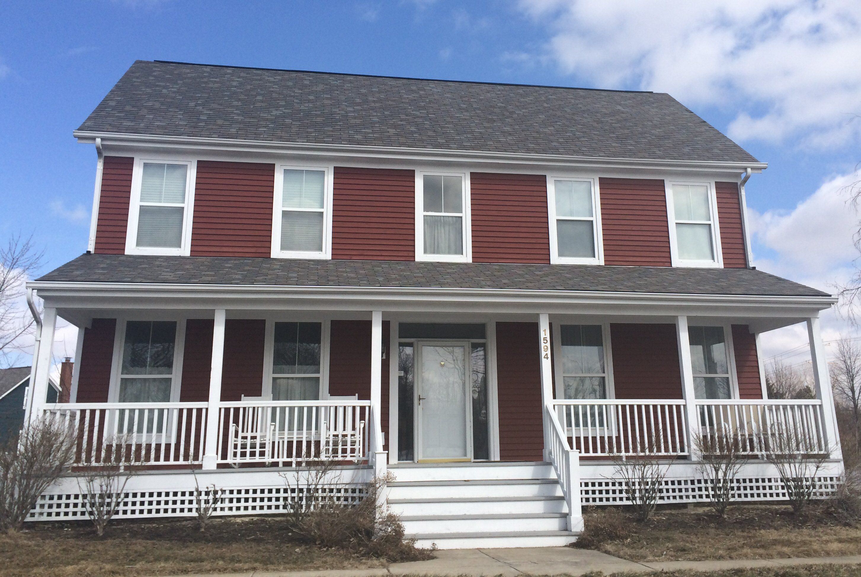 Two Story Red House With White Porch And Trim